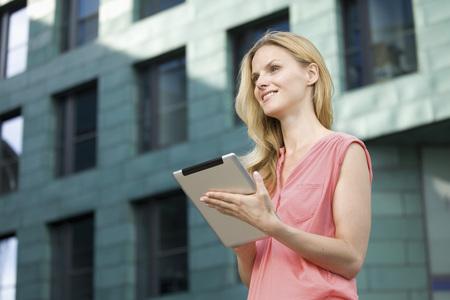 Europe,Germany,North Rhine Westphalia,Duesseldorf,Businesswoman Using Digital Tablet,Smiling