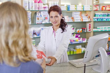 Germany,Brandenburg,Pharmacist Handing Medicne To Woman