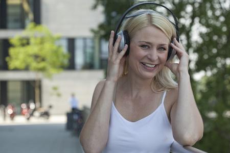 Alemania, rin-westfalia del norte, duesseldorf, mujer adulta media, con, auriculares, sonriente LANG_EVOIMAGES