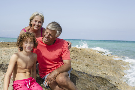 Spain,Grandparents With Grandson Sitting On Beach,Smiling