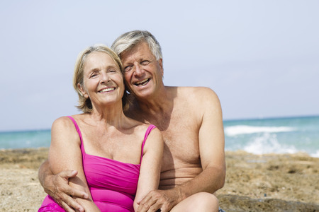 Spain,Senior Couple Sitting On Rock At Beach,Smiling