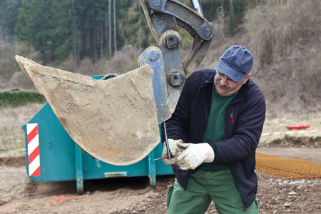 Europe,Germany,Rhineland-Palatinate,Mature Man Changing Excavator Shovel