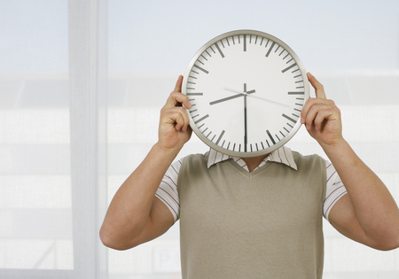 Young Man Holding Clock In Front Of Head,Close Up LANG_EVOIMAGES