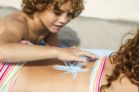 Spain,Brother Drawing On Sisters Back With Suncream