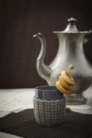 Baked Doughnuts With Cup,Tea Pot And Warmer On Table