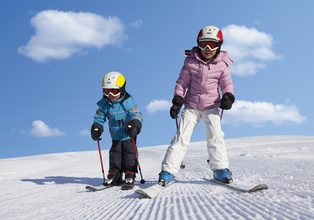 Switzerland,Boy And Girl Skiing In Snow