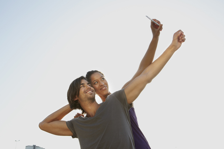 Germany,Cologne,Couple Taking Self Photograph With Mobile,Smiling