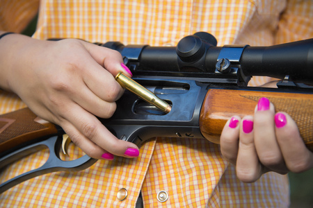 Usa,Texas,Young Woman Inserting Bullet In Hunting Rifle LANG_EVOIMAGES