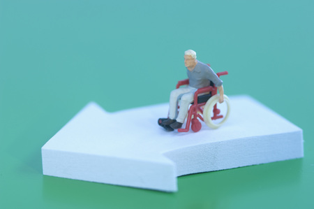 Figurine In Wheelchair With Arrow Sign On Green Background