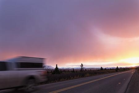 Usa,Alaska,Car Passing On Denali Park Road At Sunset LANG_EVOIMAGES