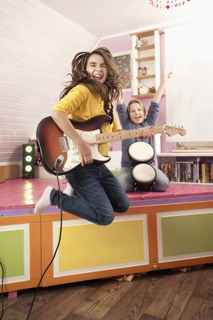 Girls Jumping While Playing Guitar And Drums
