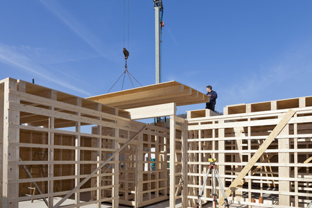 Europe,Germany,Rhineland Palantinate,Man Installing And Fixing Wooden Walls Of Prefabricated House