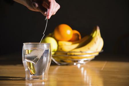 Human Hand Preparing Tea,Bowl Of Fruits In Background