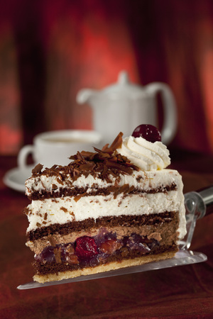 Slice Of Black Forest Cake On Cake Server,Cup Of Coffee In Background
