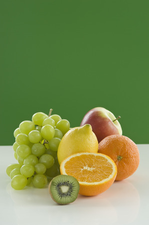 Variety Of Fruits On Table Against Green Background,Close Up