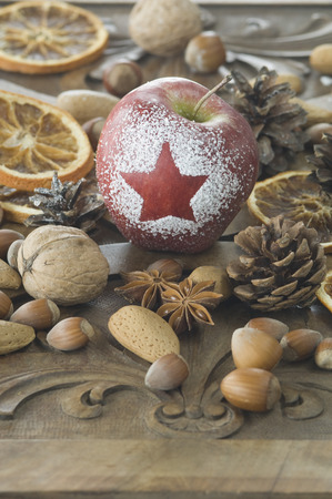 Christmas Apple With Snow Star,Hazelnuts,Walnuts,Almonds,Star Anise And Pine Cones On Table LANG_EVOIMAGES