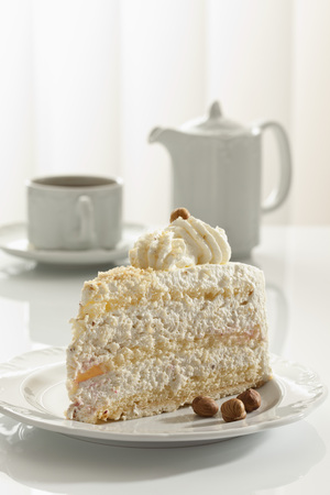 Slice Of Nut Cream Cake On Plate,Teapot And Cup In Background