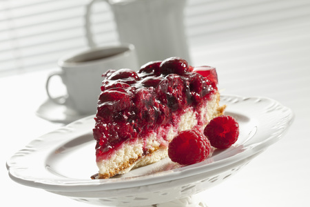 Slice Of Raspberry Cake On Cakestand And Coffee Set In Background,Close Up