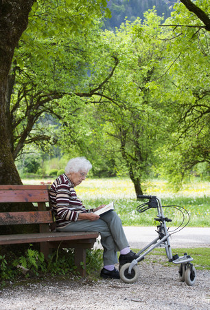 Austria,Senior Woman Sitting On Bench And Reading Book