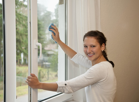 Germany,Brandenburg,Young Woman Cleaning Window LANG_EVOIMAGES