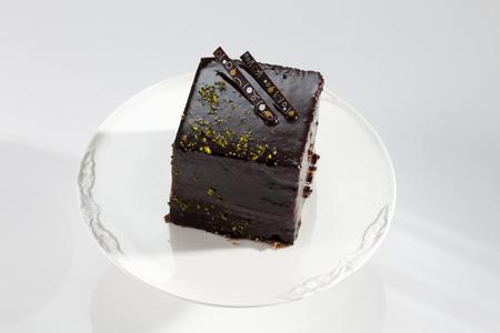 Plate Of Dark Chocolate Cake On White Background,Close Up