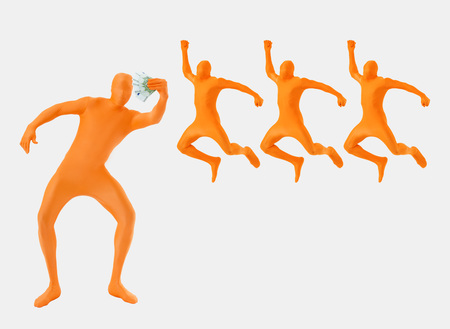 Man Standing Holding Money In Orange Zentai While Three Men Jumping In Background