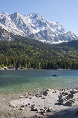 Germany,Bavaria,View Of Lake Eibsee With Tourist In Paddleboat And Zugspitze In Background LANG_EVOIMAGES