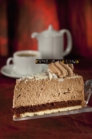 Slice Of Chocolate Cream Cake On Cake Server,Coffee Set In Background
