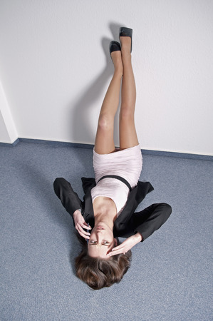 Germany, Berlin, Businesswoman Lying On Floor And Talking On Mobile Phone LANG_EVOIMAGES