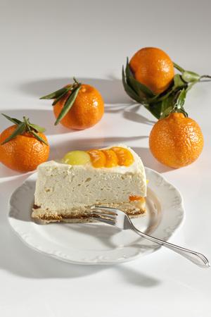 Plate Of Mandarin Cream Cake Besides Mandarins On White Background,Close Up