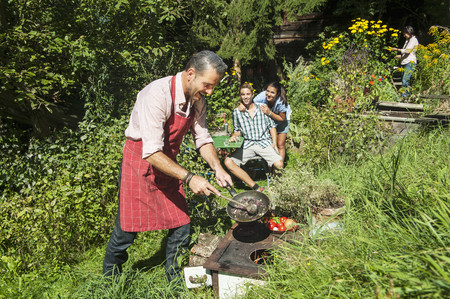Austria, Salzburg Country, Man Cooking For His Family In Garden