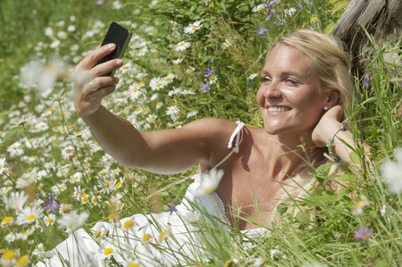 Austria, Salzburg, Mid Adult Woman With Cell Phone In Meadow, Smiling