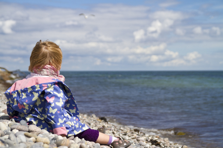 Denmark,Girl Sitting On Beach And Looking Over Blue Water LANG_EVOIMAGES