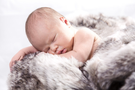 Baby On Fur In Wooden Crate LANG_EVOIMAGES