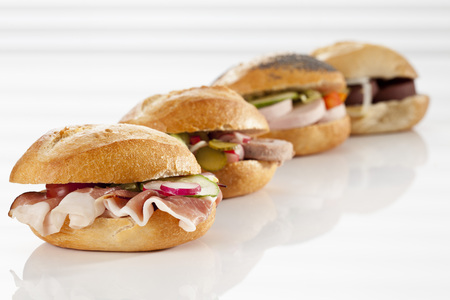 Variety Of Bread Rolls Sandwiches With Mixed Cold Cuts On White Background, Close Up