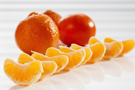 Pieces Of Peeled Mandarin And Mandarins In Background,Close Up LANG_EVOIMAGES