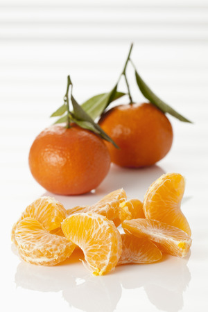 Whole And Peeled Fresh Clementines On White Background, Close Up LANG_EVOIMAGES