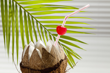 Coconut With Drinking Straw, Cherry And Palm Leaf In Background, Close Up
