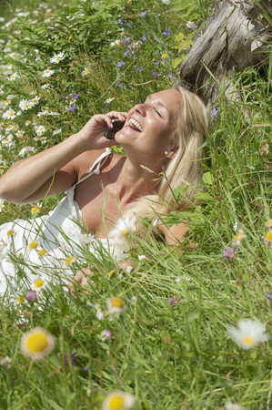 Austria, Salzburg, Mid Adult Woman Talking On Cell Phone In Meadow, Smiling