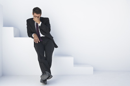Businessman In Black Suit Sitting On Stairs With Head In Hand