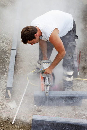 Germany,Rhineland Palatinate,Worker Cutting Paving Stone With Disc Grinder