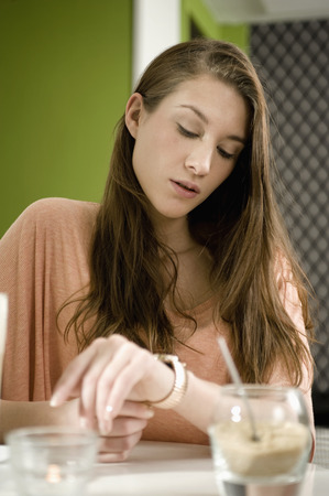 Germany,Bavaria,Munich,Young Woman Sitting At Table In Cafe,Checking Time