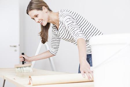 Woman Applying Glue On Wallpaper LANG_EVOIMAGES
