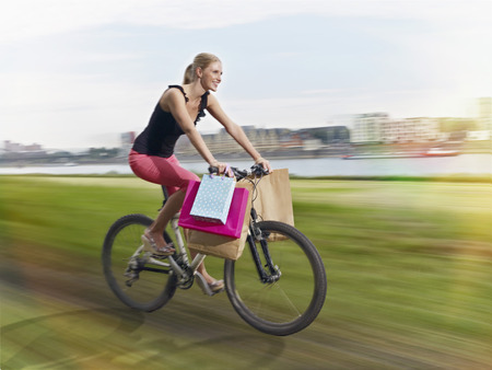 Germany,Cologne,Young Woman On Bicycle With Shopping Bags