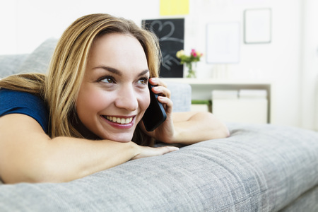 Germany,Bavaria,Munich,Young Woman Talking On Mobile Phone,Smiling LANG_EVOIMAGES