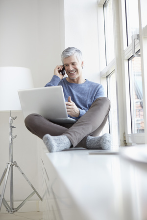 Germany,Bavaria,Munich,Mature Man Talking On Mobile And Using Laptop,Smiling LANG_EVOIMAGES