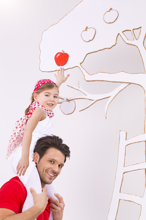 Girl Sitting On Fathers Shoulder And Trying To Pick Apple From Tree,Smiling LANG_EVOIMAGES