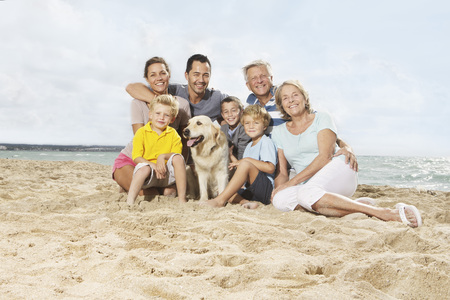 Spain,Portrait Of Family Sitting On Beach At Palma De Mallorca,Smiling