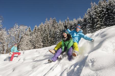 Austria,Salzburg,Young Man And Women With Sledge In Snow At Altenmarkt Zauchensee