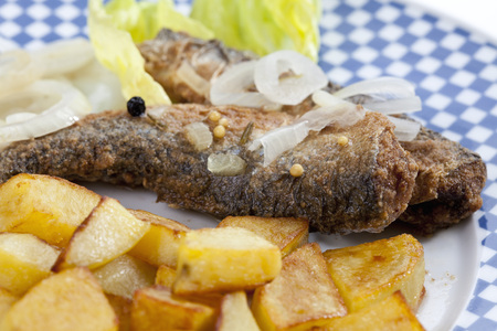 Fried Herring With Roasted Potatoes And Onions On A Plate
